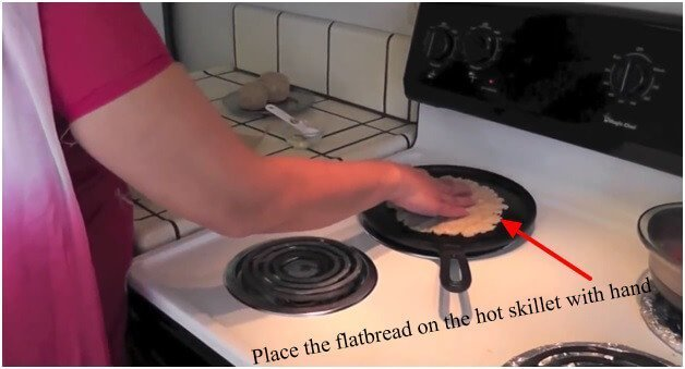 Place-the-flatbread-on-the-hot-skillet-with-hand